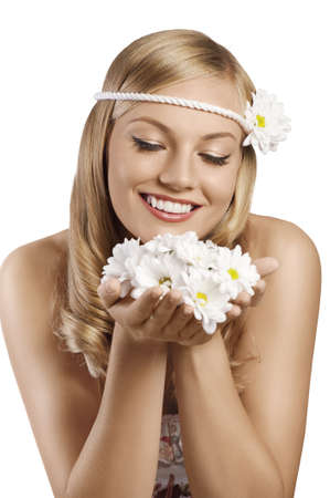sweet portrait of an attractive young blond girl with an old fashion look with a daisy in the hair and a flowered dress with flowers in hands against white background photo