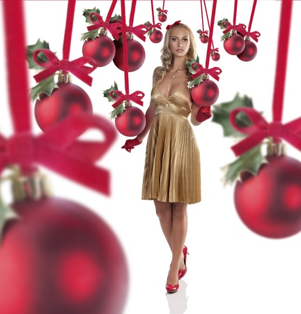 gorgeous blonde girl in elegant champagne color dress, red high heels and red gloves posing for christmas photo