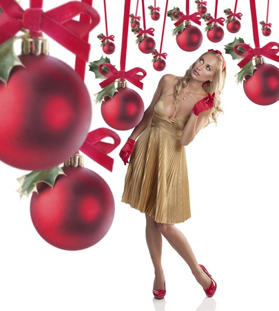 very beautiful fashion girl wearing a golden dress with red shoes, gloves and a red hair bow looking at christmas balls Stock Photo - 11169667