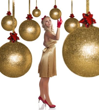bow hair: elegante tiro de Navidad de una muchacha hermosa con un vestido dorado, zapatos de tac�n alto de color rojo, guantes rojos y un mo�o llegar a una bola de navidad