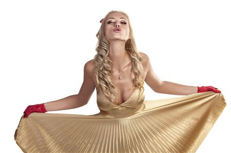very pretty girl dressed in an elegant golden satin dress for christmas with red gloves blowing a kiss to the camera photo