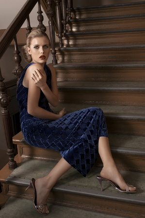 fashion shot of a pretty elegant girl sitting on stairs photo