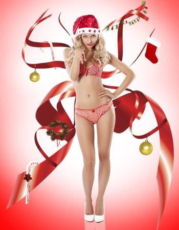 hat nude: Blond young sexy girl in red lingerie posing like a pinup and wearing a santa claus hat and high heel looking like christmas spirit