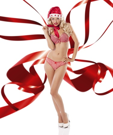 Blond young sexy girl in red lingerie posing like a pinup and wearing a santa claus hat and high heels with red ribbon wings Stock Photo - 11303189