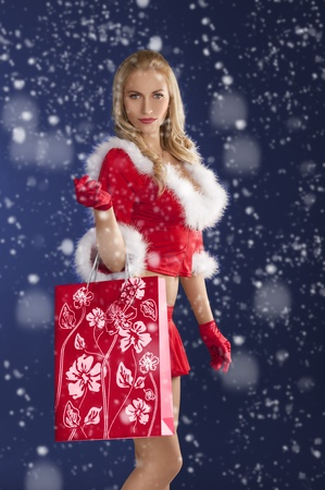 cute sexy girl in red christmas dress with fur and gloves standing with red shopping bag in hand photo