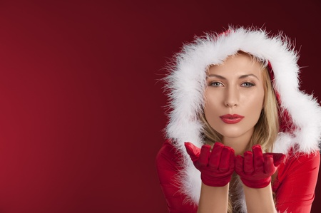 portrait of cute sexy girl in red christmas dress with fur and gloves posing photo