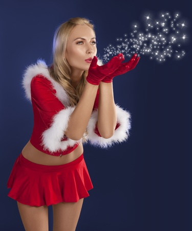 cute sexy girl in red christmas dress with fur and gloves standing while blowing air photo