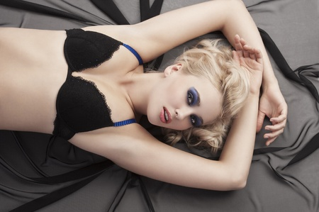 Sexy blond girl in black- blue bikini lingerie with hair style laying down on black material taking pose Stock Photo - 11303315