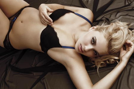 Sexy blond woman in black bikini lingerie with hair style laying down on black material taking pose Stock Photo - 11303325