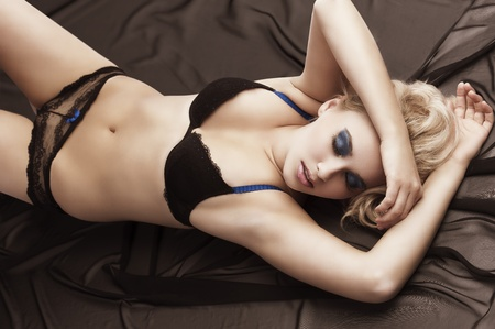 Sexy blond girl in black bikini lingerie with hair style laying down on chocolate colour material taking pose Stock Photo