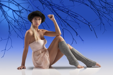 young pretty woman in a sexy pink dancer dress with fur hat and grey wool tights socks sitting on stage floor photo