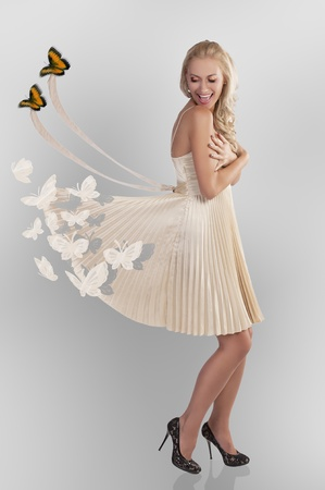 beautiful young woman in golden dress with butterfly all around playing with her elegant skirt  photo