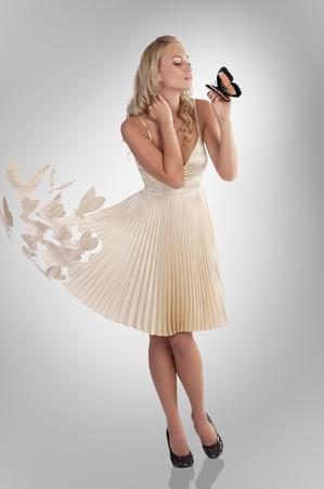 femme papillon: belle jeune femme en robe tenant un papillon et d'embrasser le m�me insecte