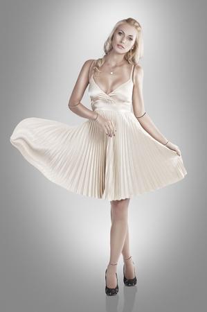 beautiful young woman looking like a porcelain doll wearing a skin colour dress Standard-Bild