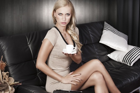 young attractive sexy blond girl sitting on a black sofa wearing a short dress photo