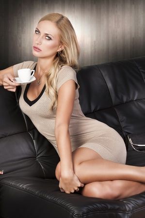 young attractive sexy blond girl sitting on a black sofa wearing a short dress and drinking from a cup. she takes the cup with right hand and has left hand near lef knee. photo