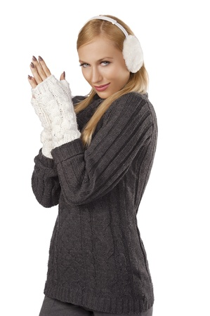 young pretty woman wearing white earmuffs and gray wool sweater be ready to go out in a cold winter day  standing  and feeling cold  against white background photo