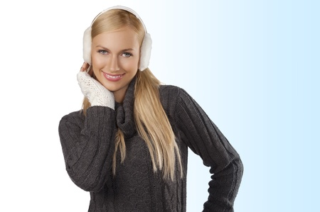 young pretty woman wearing white earmuffs and gray wool sweater be ready to go out in a cold winter day against white background  photo