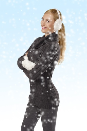 young pretty woman wearing white earmuffs and gray wool sweater be ready to go out in a cold winter day standing against white background photo
