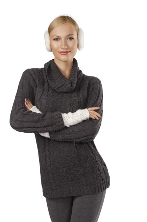 woman sweater: young pretty woman wearing white earmuffs and gray wool sweater be ready to go out in a cold winter day standing and looking at the camera against white background Stock Photo