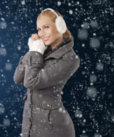 young pretty woman wearing white earmuffs and gray wool sweater be ready to go out in a cold winter day posing against gray background photo