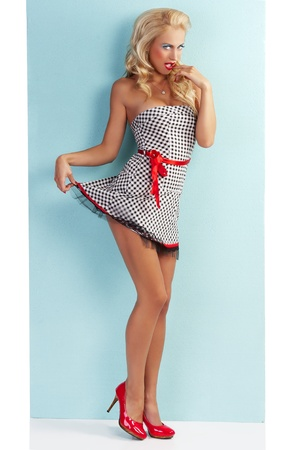 pinup style portrait of a beautiful and sexy blond girl wearing a very short dress black and white with red belt and blue eye makeup Stock Photo