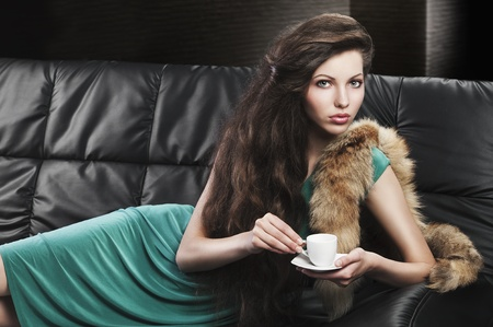young elegant lady laying down on sofa keeping and drinking from a little cup of coffee. wearing green dress.she is lying on the sofa and takes the cup with both hands. photo