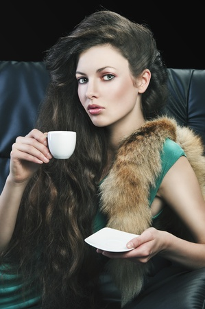 young elegant lady laying down on sofa keeping and drinking from a little cup of coffee. wearing green dress. She looks in to the lens, with right hand takes the cup and has saucer in left hand. photo