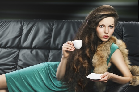 tastes: young elegant lady laying down on sofa keeping and drinking from a little cup of coffee. wearing green dress. she is lying on the sofa, looks in to the lens and takes a cup with right hand and saucer with left hand. Stock Photo