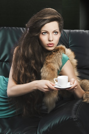 young elegant lady laying down on sofa keeping and drinking from a little cup of coffee. wearing green dress. she looks at the left and takes the cup with both hand photo