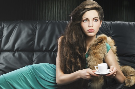 young elegant lady laying down on sofa keeping and drinking from a little cup of coffee. wearing green dress. she is lying on the sofa, looks at the left and takes the cup with both hands. photo