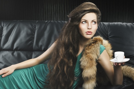 young elegant lady laying down on sofa keeping and drinking from a little cup of coffee. wearing green dress. shes lying on the sofa, looks at the left and takes a cup with left hand. photo
