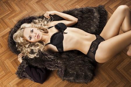erg mooi blond en sexy jonge vrouw in ondergoed tot vaststelling van de op de vloer en die met bont, ze kijkt in de lens, haar lichaam is bijna volledig blootgelegd en haar armen zijn open