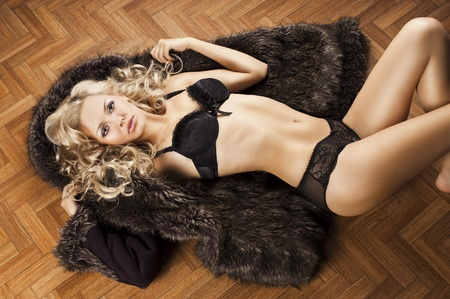 very beautiful blond and sexy young woman in underwear laying down on floor and covering with fur, she looks in to the lens, her body is almost totally uncovered and her arms are open Stock Photo