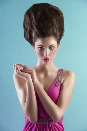 very elegant young pretty wearing a pink long dress with creative hair style over light turquoise background