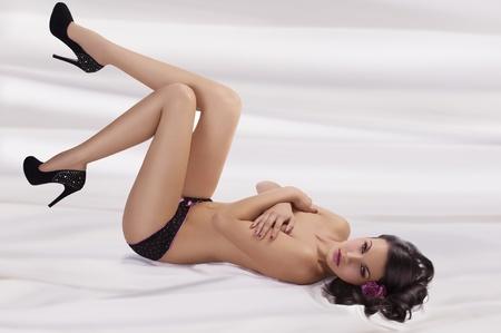 sexy girl nue: tr�s sexy brunette avec de belles jambes, fixant sur la feuille blanche nue lingerie porter et talon haut avec pose vers la cam�ra