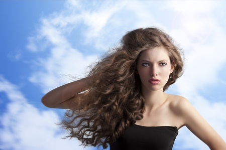 beauty fashion portrait of a very young cute brunette with long curly hair with hairstyle flying in the wind on sky background photo
