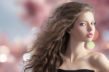beauty fashion portrait of a very young cute brunette with long curly hair with hairstyle flying in the wind on cherry blossom bokeh background Stock Photo