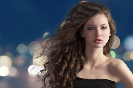 curls: beauty fashion portrait of a very young cute brunette with long curly hair with hairstyle flying in the wind on city light bokeh