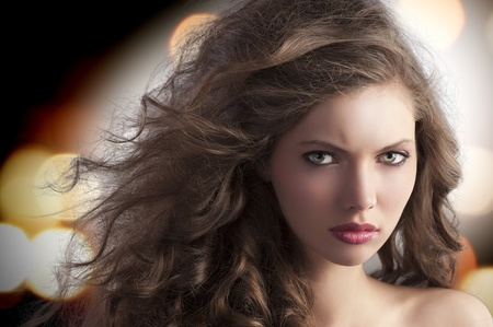 beauty fashion portrait of a very young alluring brunette with long curly hair with hairstyle flying in the wind photo