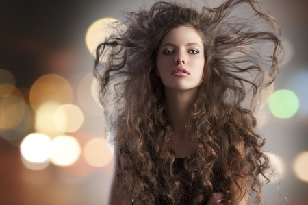 beauty fashion portrait of a very young cute alluring brunette with long curly hair with hairstyle flying in the wind and city lights