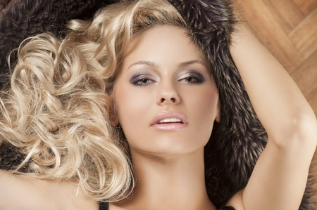close up portarit of young  alluring beautiful girl with blond curly hair wearing a black bra with fur around her photo