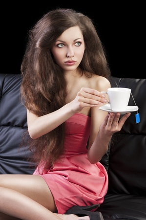 sophisticated young pretty brunette in pink elegant dress sitting on a black sofa and tasting a cup of tea. she looks at left and takes one cup of tea with both hands photo