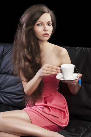 sophisticated young pretty brunette in pink elegant dress sitting on a black sofa and tasting a cup of tea. she looks in to the lens, takes the cup of tea with both hands and her legs are bent on the sofa. photo