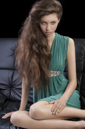 young elegant woman sitting on a black sofa with hair style and wearing a green dress looking in camera photo