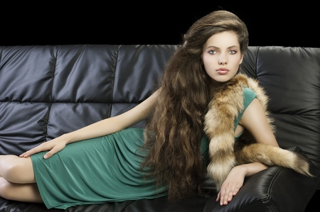 sophisticated elegant woman laying on a black sofa with hair style and wearing a green dress and a tail fur looking in camera photo