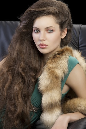 portrait of a sophisticated elegant woman sitting on a black sofa with hair style and wearing a green dress and a tail fur looking in camera photo