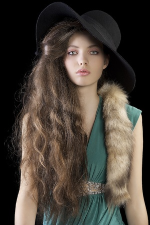sophisticated elegant woman portrait with hair style and wearing a green dress and a tail fur , black hat photo