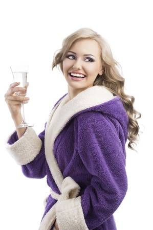 blond pretty expressive blond girl in purple bathrobe drinking from a glass of white wine happy, she laughs and looks at left, takes the glass with right hand photo