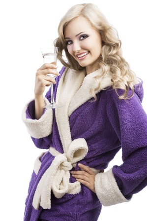 blond pretty expressive blond girl in purple bathrobe drinking from a glass of white wine happy, she looks in to the lens, laughs and has her left hand on her left hip and takes the glass with right hand photo